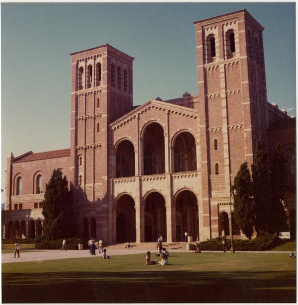 Students sitting on grass and walking by Royce Hall