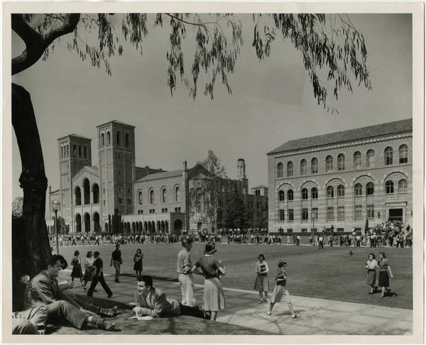Northwest view of Royce Hall and Haines Hall as students walk and sit in main quadrangle between classes