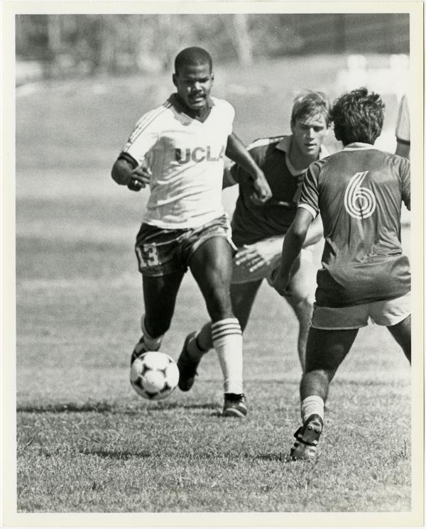UCLA soccer player, Mark Clay, dribbling ball past opponents