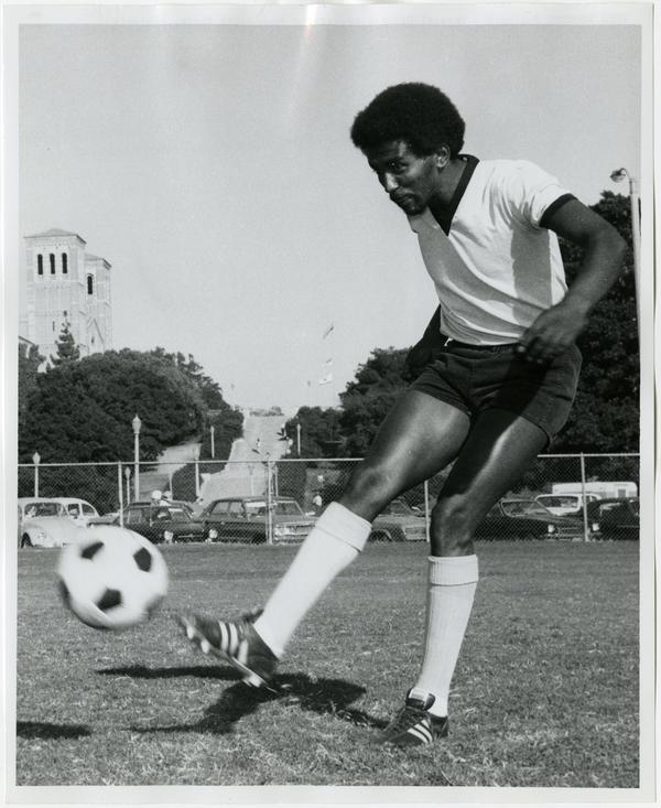 UCLA soccer fullback, Yaregal Gebreyesus, kicking soccer ball, ca. 1973