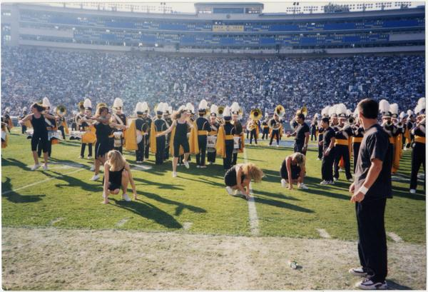 Spirit Squad performing at game with marching band in background, ca. November 1998