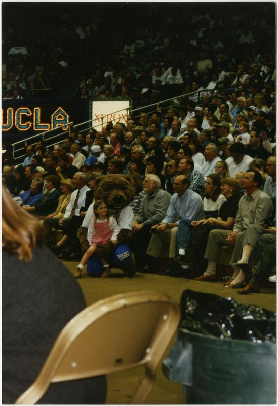 Girl sitting on Joe Bruin's lap at basketball game, ca. February 1997