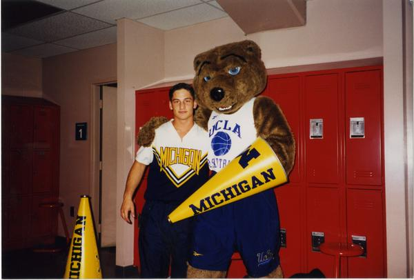 Joe Bruin with member of Michigan Spirit Squad in locker room, ca. March 1998