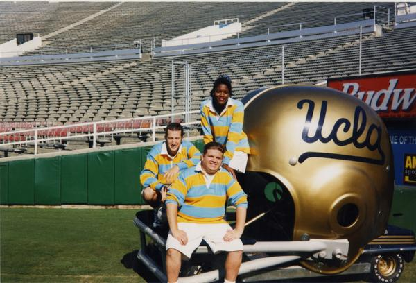 Members of Spirit Squad posing on field by a large UCLA football helmet