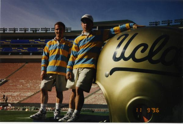 Members of Spirit Squad posing on field by a large UCLA football helmet, ca. 1996