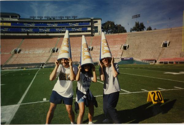 Members of Spirit Squad posing on field with megaphones on heads