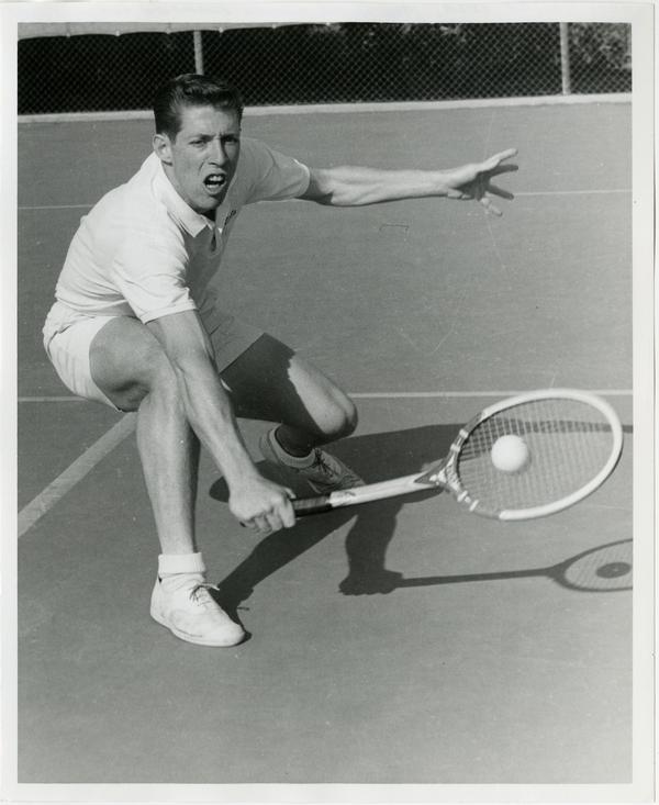 NCAA champion, Larry Nagler, hitting ball with raquet, ca. 1960s