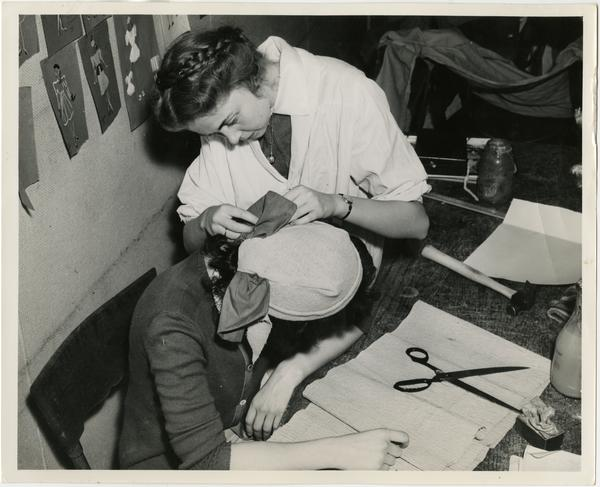 "Students constructing a hat to be used in a play in ""Green Room"" of Theater Arts Department"