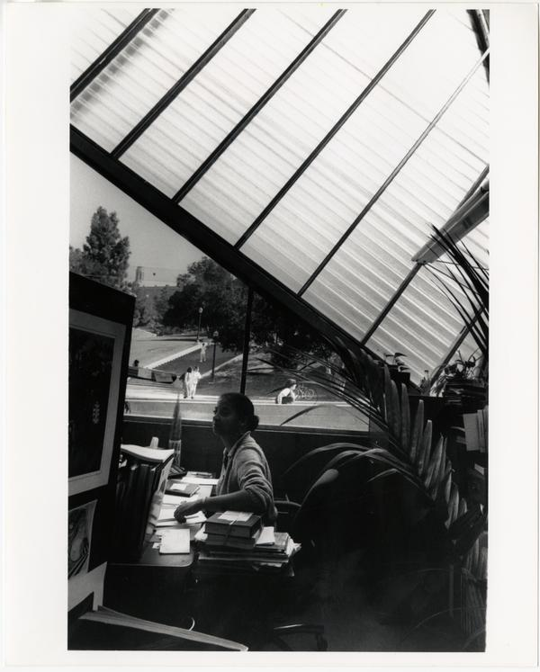 View of Library staff member at desk in Temporary Powell Library with Janss Steps visible in background