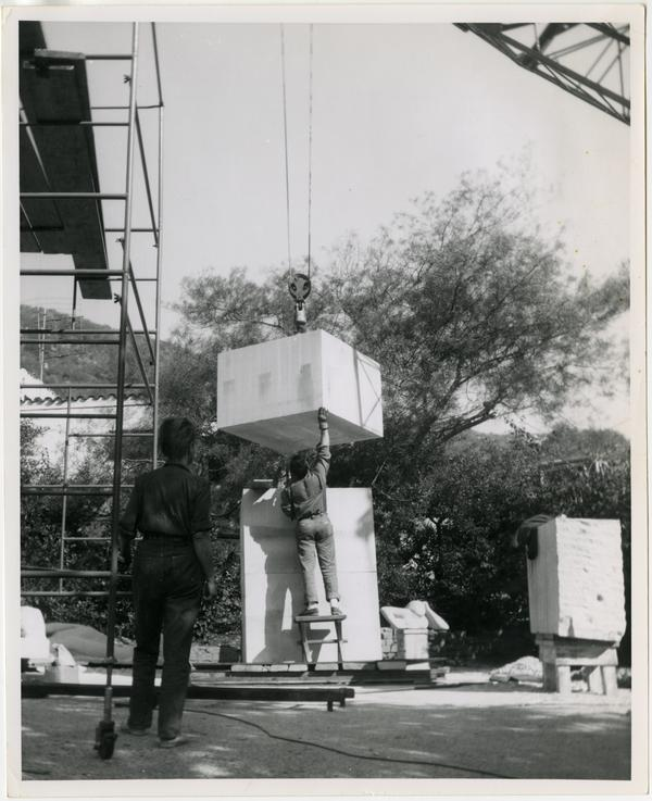 Installation of limestone column for Anna Mahler's scultpture with her back to camera