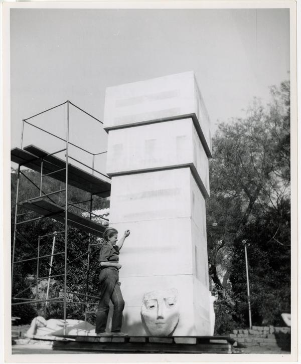 Anna Mahler standing beside fifteen foot limestone column with clay model sketch before sculpting