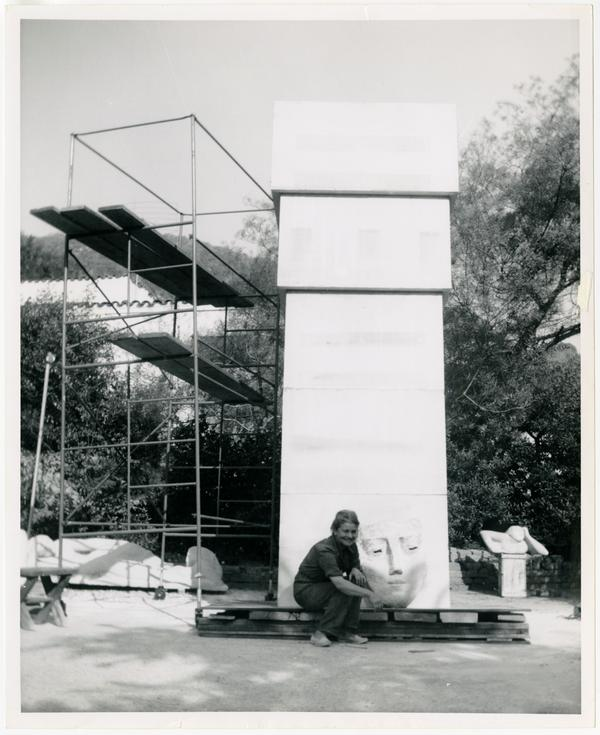 Anna Mahler sitting beside fifteen foot limestone column with clay model sketch before sculpting