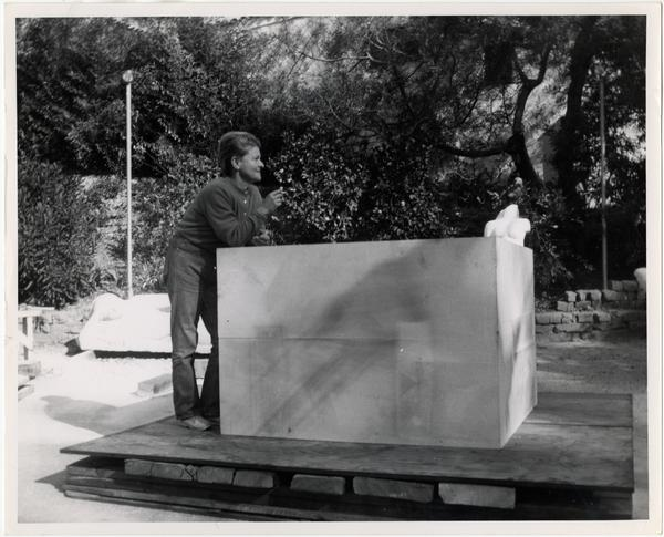 Anna Mahler standing beside limestone block during installation of column
