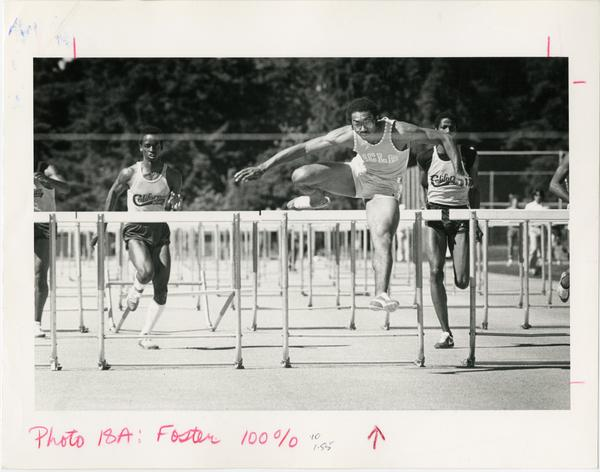 Greg Foster jumping over hurdle, ca. 1971