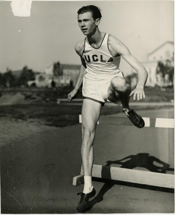 Carl McBain jumping over hurdle, ca. 1940