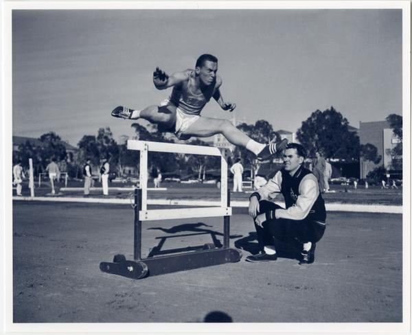 Track team member jumping over hurdle