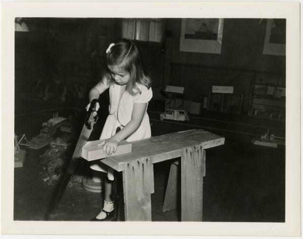 Child sawing piece of wood at Training School