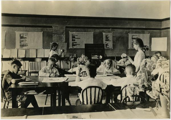 Children sitting at tables in classroom of Training School, ca. 1920