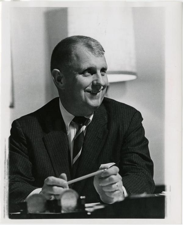 Doug Kinsey sitting at desk with pencil in hand