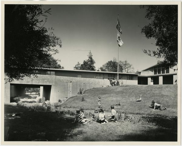 Children playing on grass with ducks and geese, ca. 1951