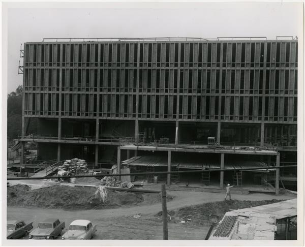 Construction worker walking in front of construction of the University Research Library