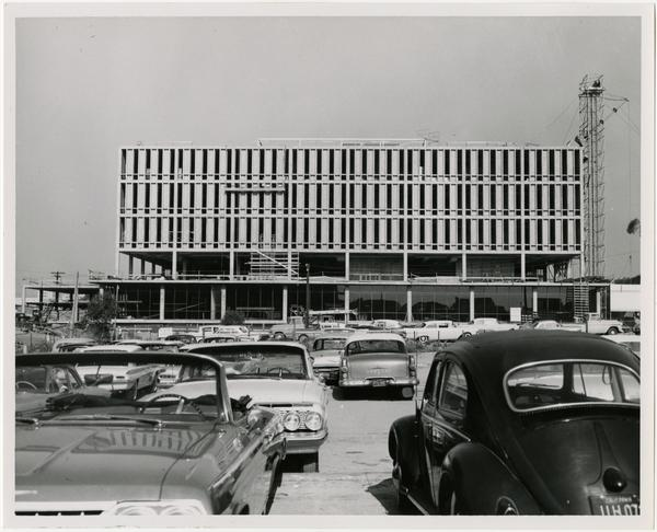 View of cars parked with construction of University Research Library in the background