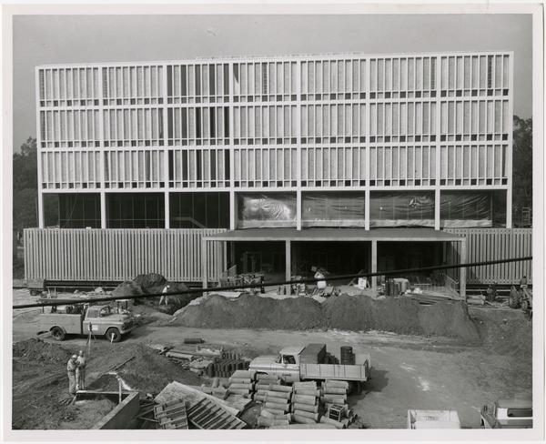 Frontal view of construction of the University Research Library with workers in the foreground