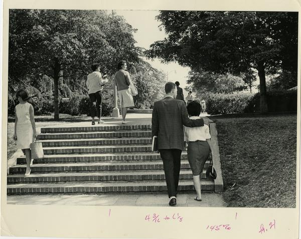 Students walking up stairs on campus, ca. 1964
