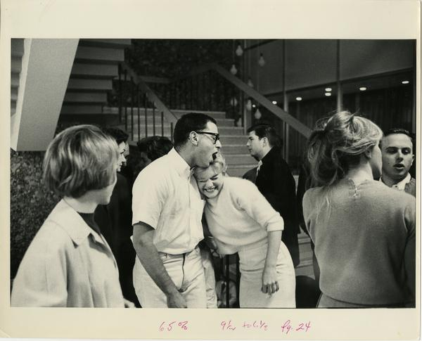 Students hugging beside a stair case, ca. 1964