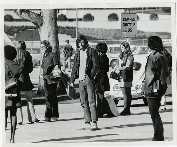 Students at campus shuttle bus stop, ca. 1975