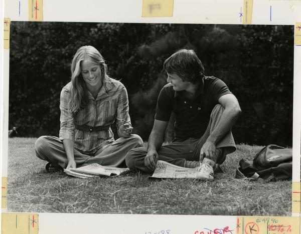 Student couple sitting on grass, ca. 1980's