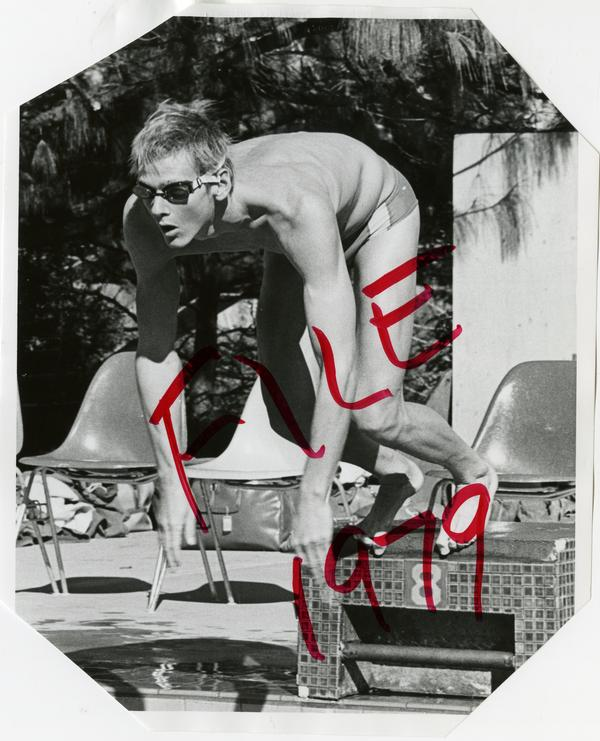 UCLA swim team member, Daniel Stephenson, jumping into pool from starting position, ca. 1979