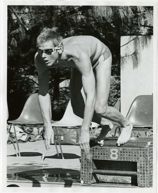 UCLA swim team member, Daniel Stephenson, jumping into pool from starting position, ca. 1979