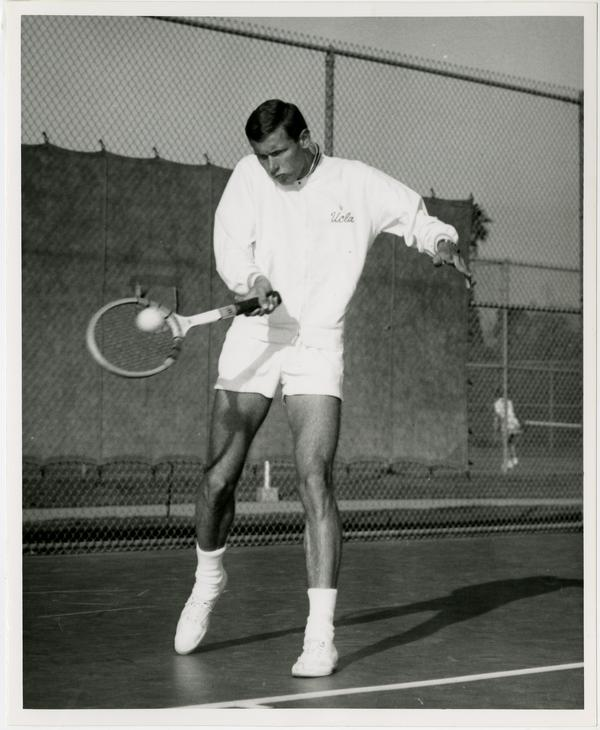 UCLA tennis team member, Dave Reed, hitting ball with raquet