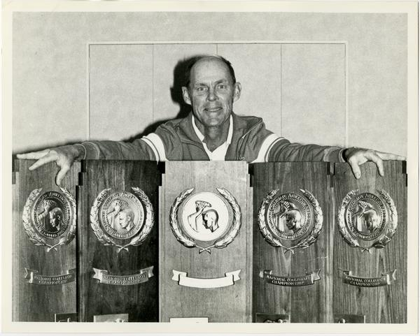 Coach holding NCAA awards, ca. 1982