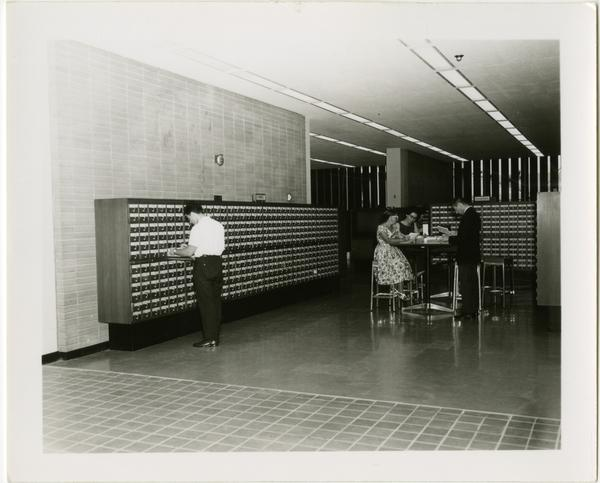 One student looks through the card catalog while other students study at a table in the University Research Library
