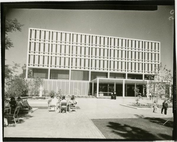 Students sitting at tables in front of the University Research Library