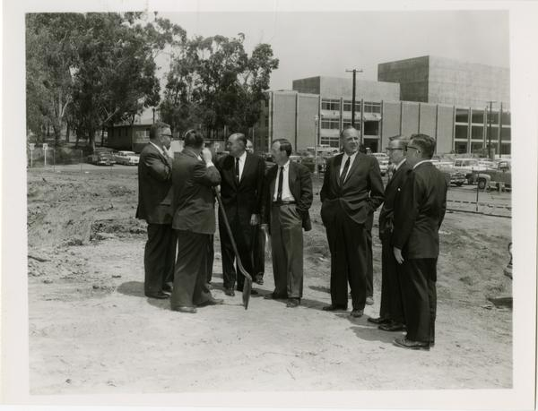 William G. Young, Robert Vosper and others talking amongst themselves on the site of the new University Research Library during the groundbreaking ceremony, April 26, 1926