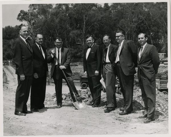 William G. Young, Robert Vosper and others posing on the site of the new University Research Library during the groundbreaking ceremony