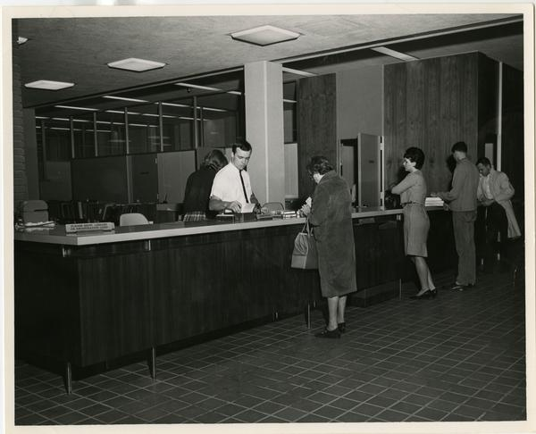 Patrons at the reference desk at the University Research Library, ca. 1964