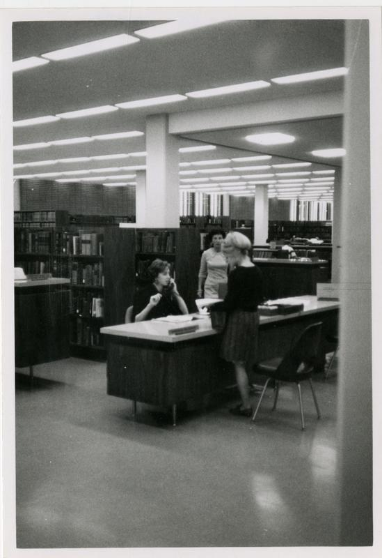 Part of the reference staff sitting at reference desks in a room of the University Research Library, ca. 1968