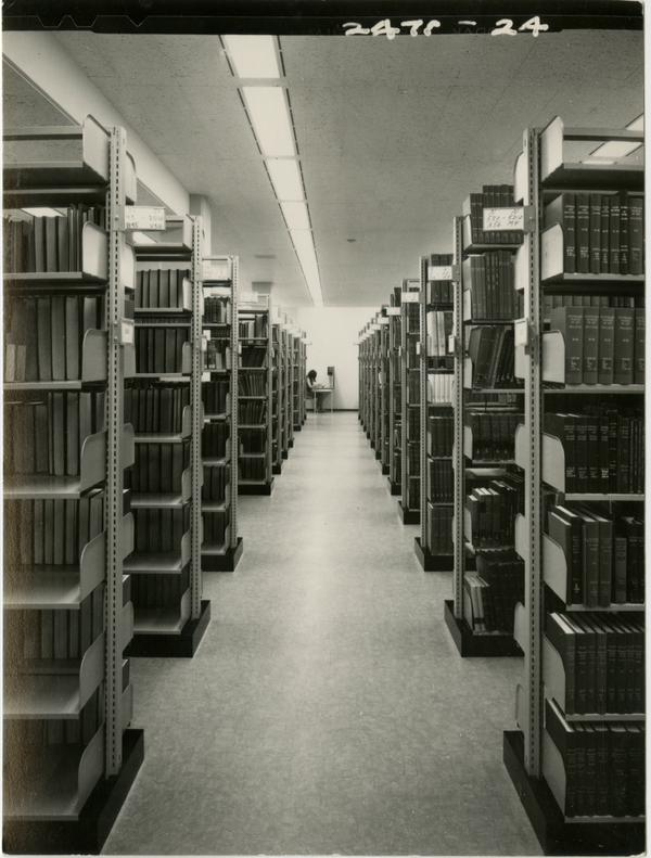 Library stacks with a student working at a desk in the background, ca. 1964