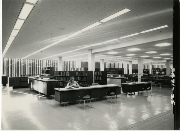 Reference staff member sits at the reference desk at the University Research Library, ca. 1964