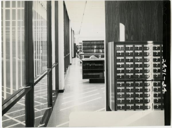 Looking down the interior wall of the University Research Library past the card catalog boxes to the stacks, ca. 1964