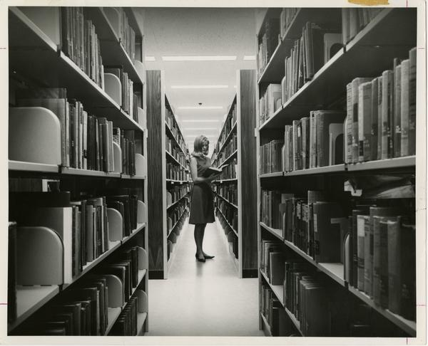 Woman standing between two library stacks examining a book in the University Research Library, ca. 1964