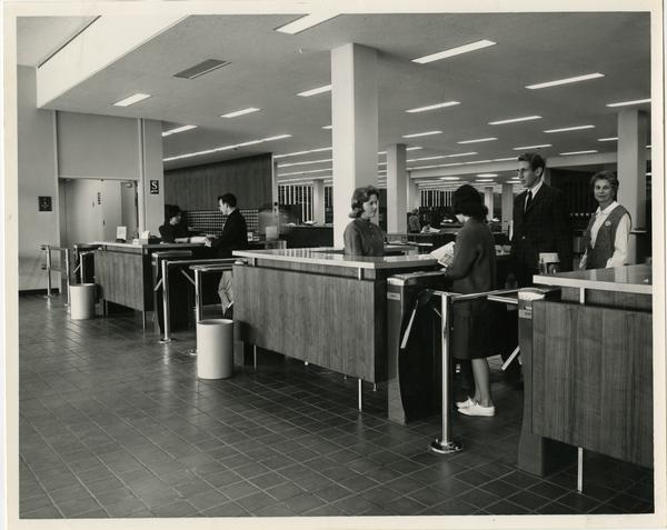 Students waiting in line to talk to library staff workers before exiting the University Resarch Library, ca. 1964