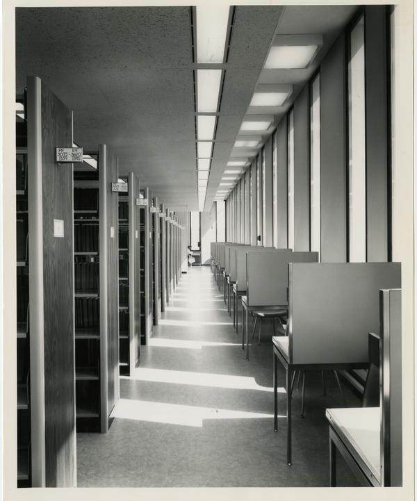 Desks lined up next to a stack in the University Research Library, ca. 1964