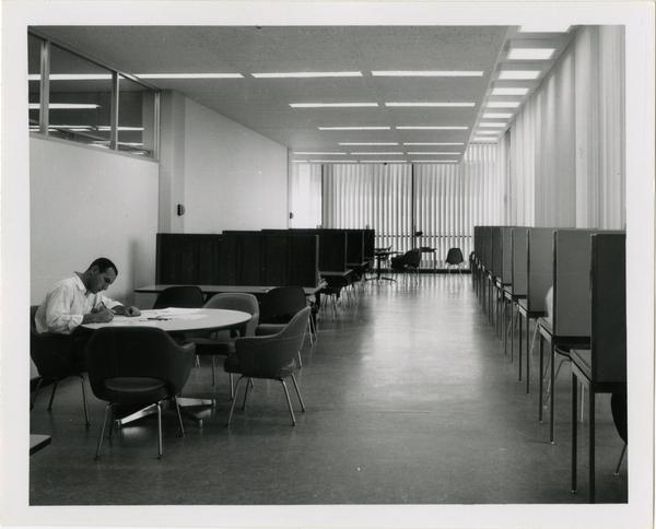 View of student working at table in University Research Library surrounded by study cubicles