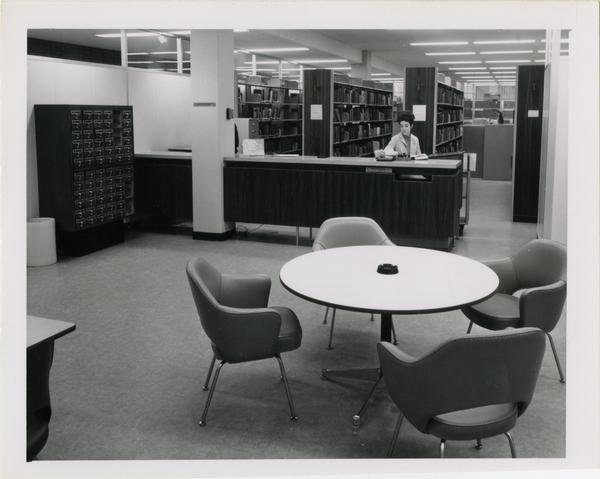 Library employee seated behind desk, ca. 1964