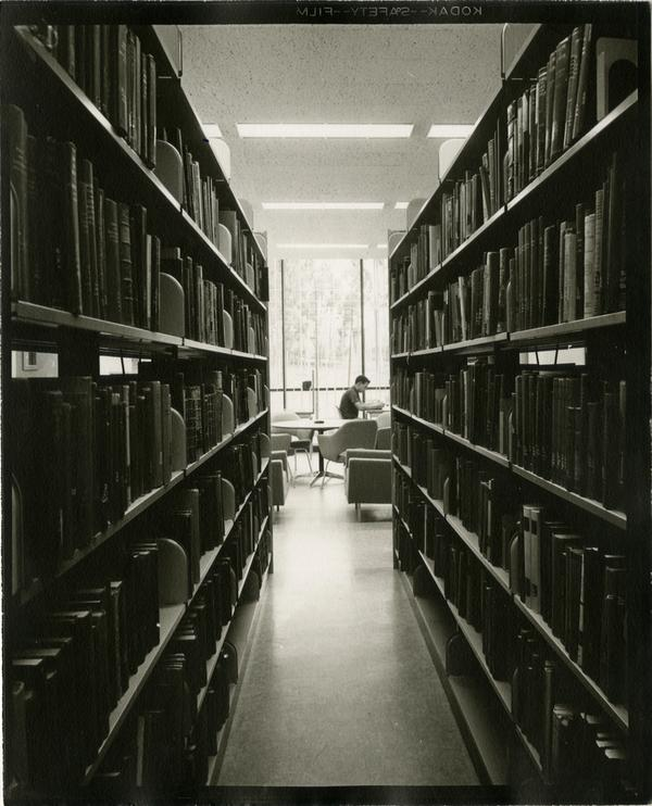 Contact print of student sitting at desk at the end of stacks, ca. 1964